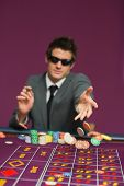 Man throwing chips on roulette table in casino