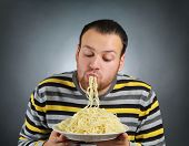 stock photo of greed  - funny young man eating pasta - JPG