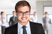Retrato de um empresário bonitão na frente de sua equipe