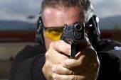 Man shooting on an outdoor shooting range, selective focus