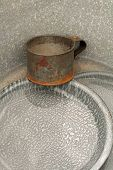 image of washtub  - A tin cup and enamel plates in a washtub - JPG