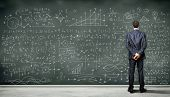 picture of frustrated  - Business person standing against the blackboard with a lot of data written on it - JPG