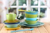 Colorful tableware on wooden table on window background