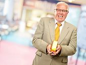 Senior Man Holding Gold Bar, Indoor