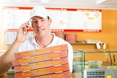 stock photo of take out pizza  - Man holding several pizza boxes in hand and asking you to order pizza for delivery - JPG