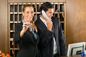 Reception in hotel - Man and woman standing at the front desk, man taking a call, woman holding a ke