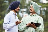 stock photo of sikh  - Two smiling authentic native indian punjabi sikh men in turban discussing something with tablet computer - JPG