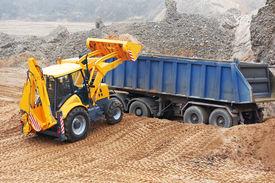 stock photo of dumper  - Wheel loader Excavator with backhoe loading sand into dumper truck at eathmoving works in construction site quarry - JPG