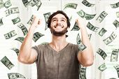 stock photo of profit  - Portrait of a very happy young man in a rain of money - JPG