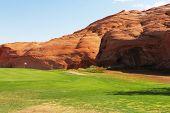 Césped verde y Cerro de piedra arenisca roja. Cercanías de la ciudad de página en los E.e.u.u.