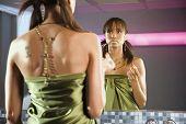 Portrait of elegant woman looking at mirror