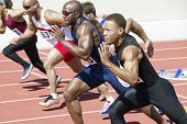 stock photo of track field  - Side view of multiethnic male athletics sprinting on running track - JPG