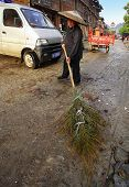 Chinese Wiper Sweeping The Main Street Of The Village Of Bamboo Besom