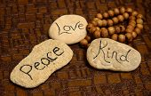 stock photo of beads  - peace love and kindness words on rocks for world peace - JPG