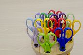 foto of blunt  - Scissors of different colorson wooden desk with copy space - JPG