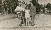 LODZ, POLAND,CIRCA FIFTIES- vintage photo of godparents with a baby in traditional baby's sleeping bag for christening, in the company of baby's grandfather and sister, Lodz, Poland, circa fifties