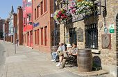 DUBLIN, IRELAND - JUNE 8: Family rests on bench in front of the oldest pub in Ireland,     The Braze