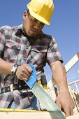 Construction worker sawing on construction site