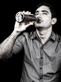 Grunge portrait of a drunk man drinking from a liquor bottle (isolated on black)
