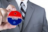 A man in a business suit holds out a political independent voter pin during elections.