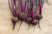 Group of fresh beets on wooden cutting board