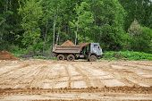 Dump-body Truck Unloads A Ground On The Land