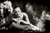Beautiful bellet dancer posing at studio over vintage background. Black-and-white.