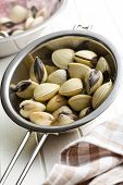 raw clams in colander on white wooden table
