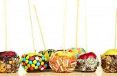 Candied apples on sticks on wooden table on white background