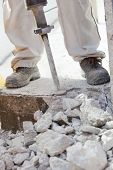 Worker Demolishing The Concrete With A Jackhammer