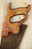 Old Rusty Saw On Wooden Background