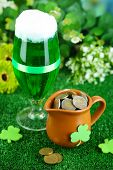 Glass of green beer and pitcher with coins on grass close-up
