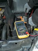 stock photo of  multimeter  - Auto mechanic measuring car battery voltage using multimeter - JPG