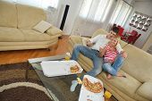 happy young couple eat fresh pizza at home relaxing and watch tv