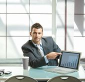 Young businessman sitting at desk presenting business diagram to others on laptop computer.
