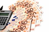 Bills of fifty Euros on a white background with pocket calculator and pen,