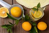 Fresh Squeezed Lemonade on a rustic wooden table with lemons, sun hat and juicer. Horizontal format