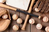 High angle shot of old and use baseball equipment on a rustic wood surface. Items include, baseballs