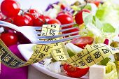 foto of measurements  - tape measure with vegetable food background, concept of diet and lose weight