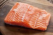 Salmon filet on a wooden carving board. Macro shot.