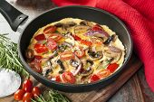 Vegetable omelet cooked in a skillet or frypan.  Mushrooms, capsicum, baby plum tomatoes and red onion.