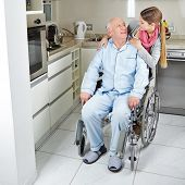 Family with senior man in wheelchair at home in the kitchen