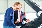 Seller or car salesman and client or customer in car dealership presenting the engine performance of