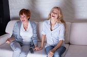 Mother with adult daughter watching television. Women looking film comedy