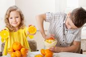 Children with oranges. Boy and girl squeezed orange juice.
