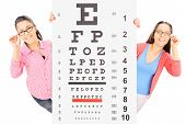 Two teenage girls with glasses standing behind an eyesight test, isolated on white background