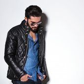 stock photo of down jacket  - side view of a fashion man in leather jacket looking down in studio - JPG