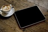 blank tablet computer on a wooden background next to a cup of coffee