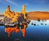 Outliers - calcareous tufa formation on the smooth water of the lake. Orange sunset. The magic of M