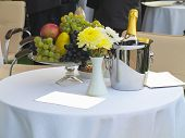 Table Set For Romantic Dinner With Champagne Flowers And Fruits